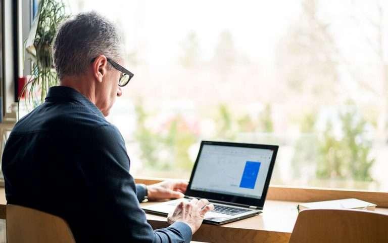 homem sentado em frente a uma mesa olhando para um notebook.