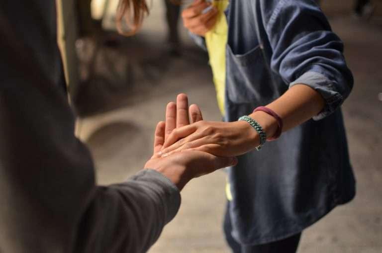 A foto mostra as mãos de duas pessoas diferentes, elas estão dando as mãos uma para a outra.